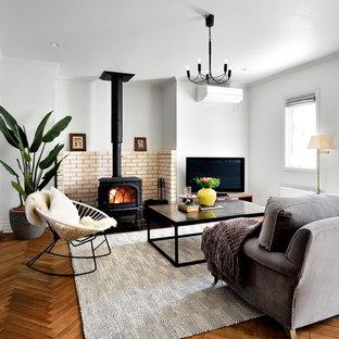 Foto de salón para visitas abierto, escandinavo, con paredes blancas, suelo de madera en tonos medios, estufa de leña, marco de chimenea de ladrillo, televisor independiente y suelo marrón