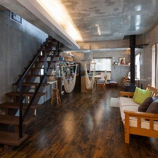 東京23区の広いインダストリアルスタイルのおしゃれなLDK (グレーの壁、クッションフロア、薪ストーブ、タイルの暖炉まわり、黒い床) の写真