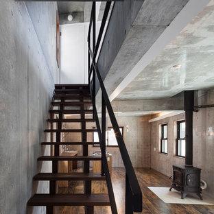 Ejemplo de salón abierto, moderno, grande, con paredes grises, suelo vinílico, estufa de leña, marco de chimenea de baldosas y/o azulejos y suelo negro