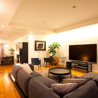 Foto di un soggiorno design con pareti bianche, pavimento in legno massello medio, TV autoportante e pavimento marrone