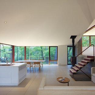 他の地域の大きいモダンスタイルのおしゃれなLDK (薪ストーブ、白い壁、セラミックタイルの床、タイルの暖炉まわり、ベージュの床) の写真
