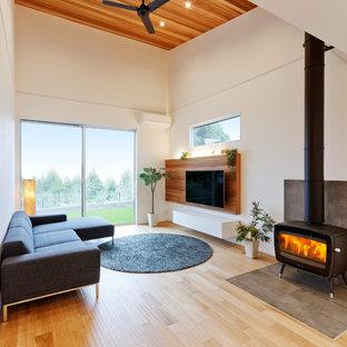 Idee per un soggiorno minimal con pareti bianche, pavimento in legno massello medio, stufa a legna, cornice del camino piastrellata, TV a parete e pavimento marrone