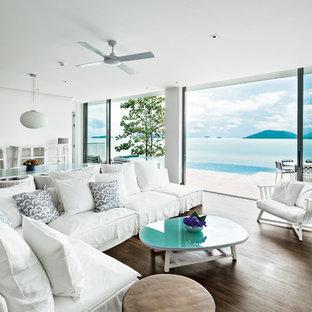 Immagine di un soggiorno stile marinaro aperto con pareti bianche e pavimento in legno verniciato