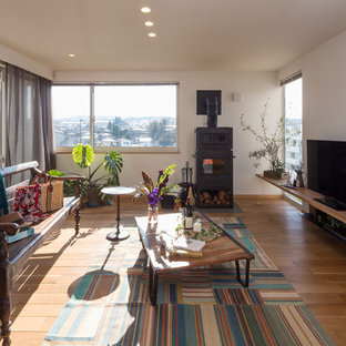 Example of an eclectic enclosed medium tone wood floor and brown floor living room design in Other with white walls, a wood stove and a tv stand