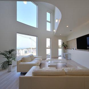 他の地域のビーチスタイルのおしゃれなリビング (白い壁、壁掛け型テレビ、ベージュの床) の写真