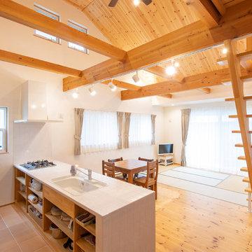 漆喰と勾配天井のパイン材に包まれた大きな吹抜けのある可愛らしい平屋