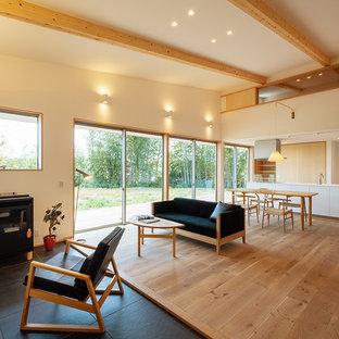 他の地域の中サイズのカントリー風おしゃれなLDK (白い壁、無垢フローリング、薪ストーブ、タイルの暖炉まわり、茶色い床) の写真
