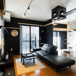 中くらいのモダンスタイルのおしゃれなリビングロフト (黒い壁、塗装フローリング、据え置き型テレビ) の写真