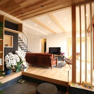 他の地域の広いトラディショナルスタイルの居間の画像 (茶色い壁、淡色無垢フローリング、ベージュの床、据え置き型テレビ)