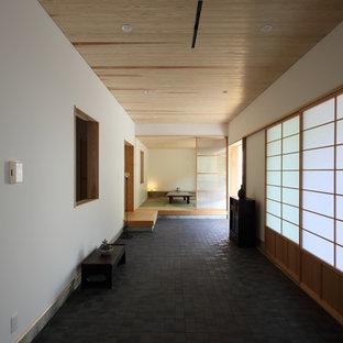 Ispirazione per un piccolo soggiorno etnico aperto con pareti bianche, pavimento in gres porcellanato, nessun camino, cornice del camino piastrellata, nessuna TV e pavimento nero