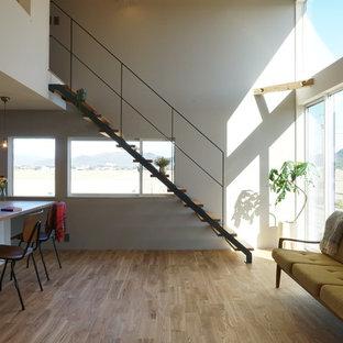 他の地域のコンテンポラリースタイルのおしゃれなリビング (白い壁、淡色無垢フローリング、ベージュの床) の写真