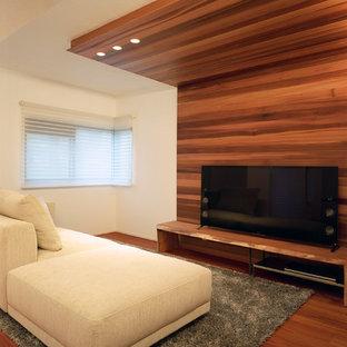 他の地域のモダンスタイルのおしゃれなリビング (マルチカラーの壁、無垢フローリング、据え置き型テレビ、茶色い床) の写真