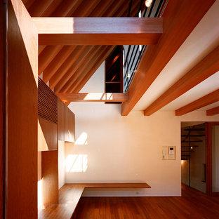 Kleines, Offenes Modernes Musikzimmer ohne Kamin mit weißer Wandfarbe, braunem Holzboden, verputztem Kaminsims, Wand-TV und braunem Boden in Tokio