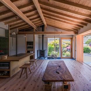 他の地域のアジアンスタイルのおしゃれなLDK (白い壁、無垢フローリング、薪ストーブ、コンクリートの暖炉まわり、壁掛け型テレビ、茶色い床) の写真