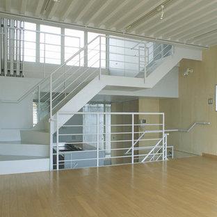 Esempio di un soggiorno minimalista con pareti beige, pavimento in compensato e pavimento beige