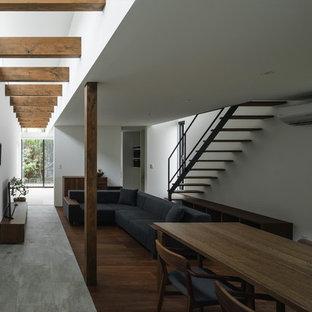 他の地域の中くらいのモダンスタイルのおしゃれなLDK (白い壁、磁器タイルの床、据え置き型テレビ、グレーの床) の写真