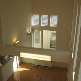 Ispirazione per un grande soggiorno moderno con pareti bianche, pavimento in compensato, nessun camino e TV autoportante