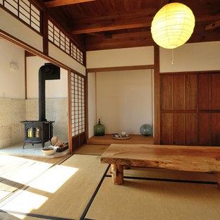 他の地域のアジアンスタイルのおしゃれなリビング (白い壁、畳、薪ストーブ、コンクリートの暖炉まわり、茶色い床) の写真