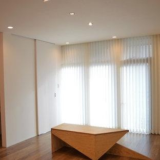 Mittelgroßes, Offenes Retro Wohnzimmer mit weißer Wandfarbe, Sperrholzboden, Wand-TV und braunem Boden in Sonstige