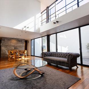 コンテンポラリースタイルのおしゃれなリビング (白い壁、無垢フローリング、暖炉なし、壁掛け型テレビ、茶色い床) の写真