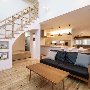北欧スタイルのおしゃれなLDK (白い壁、無垢フローリング、暖炉なし、ベージュの床) の写真
