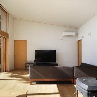 東京23区の広い和風のおしゃれなLDK (白い壁、合板フローリング、薪ストーブ、タイルの暖炉まわり、据え置き型テレビ、ベージュの床) の写真
