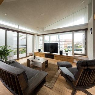 Foto de salón de estilo zen con paredes blancas, suelo de madera en tonos medios, televisor independiente y suelo marrón