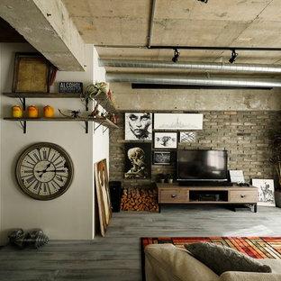 インダストリアルスタイルのおしゃれなリビング (グレーの壁、無垢フローリング、据え置き型テレビ、グレーの床) の写真