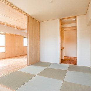 Imagen de salón abierto, minimalista, de tamaño medio, con paredes beige, tatami y suelo verde