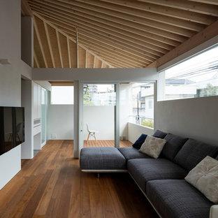 Großes, Offenes Wohnzimmer ohne Kamin mit weißer Wandfarbe, Sperrholzboden, Wand-TV und braunem Boden in Kobe
