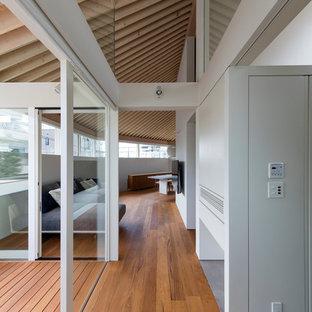 Ejemplo de salón actual, grande, sin chimenea, con paredes blancas, suelo marrón, suelo de contrachapado y televisor colgado en la pared