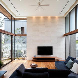 他の地域のモダンスタイルのおしゃれなリビング (ベージュの壁、無垢フローリング、壁掛け型テレビ、茶色い床) の写真