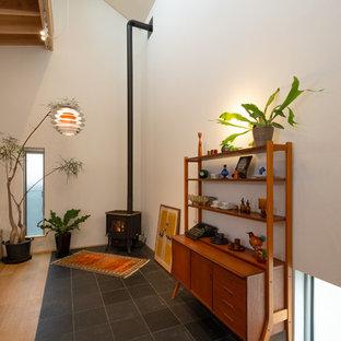 Modelo de salón abierto, minimalista, con paredes blancas, suelo de pizarra, chimenea de esquina, marco de chimenea de piedra y suelo negro