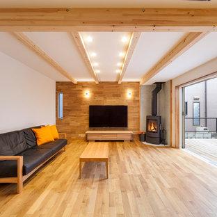 他の地域の北欧スタイルのおしゃれなリビング (白い壁、薪ストーブ、据え置き型テレビ、茶色い床) の写真