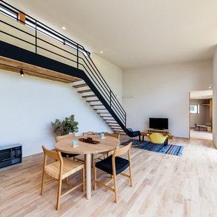 他の地域の広いコンテンポラリースタイルのおしゃれなLDK (白い壁、淡色無垢フローリング、ベージュの床、据え置き型テレビ) の写真