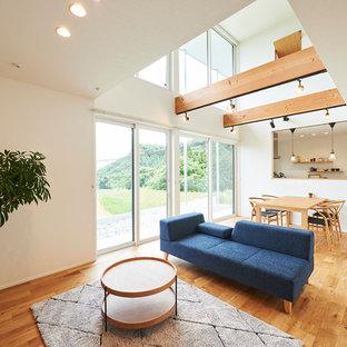 他の地域の広い北欧スタイルのおしゃれなLDK (フォーマル、白い壁、無垢フローリング、暖炉なし、据え置き型テレビ、マルチカラーの床) の写真
