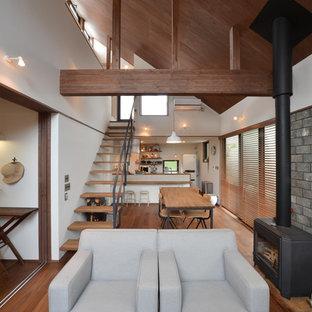Imagen de salón de estilo zen con suelo de madera en tonos medios, estufa de leña, marco de chimenea de hormigón, paredes blancas y suelo marrón