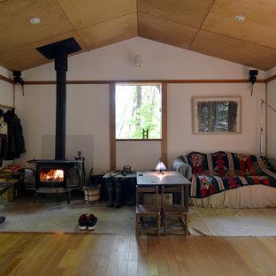 他の地域の小さい和風のおしゃれなLDK (白い壁、無垢フローリング、薪ストーブ、テレビなし、漆喰の暖炉まわり) の写真