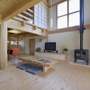 他の地域のアジアンスタイルのおしゃれなLDK (白い壁、淡色無垢フローリング、薪ストーブ、金属の暖炉まわり、据え置き型テレビ、ベージュの床) の写真