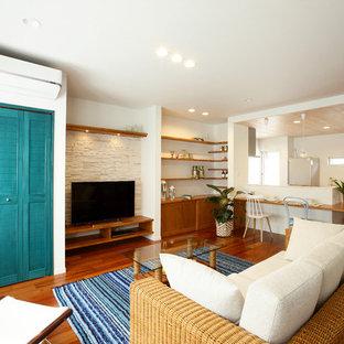 他の地域のトロピカルスタイルのおしゃれなリビング (白い壁、無垢フローリング、据え置き型テレビ、茶色い床) の写真