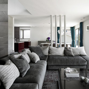 他の地域の広いコンテンポラリースタイルのおしゃれなLDK (白い壁、セラミックタイルの床、薪ストーブ、タイルの暖炉まわり、据え置き型テレビ、ベージュの床) の写真