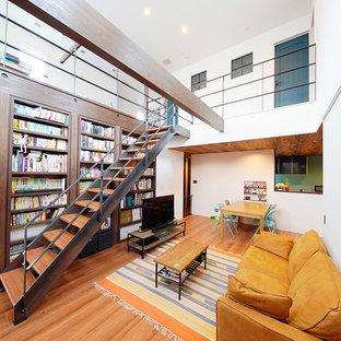 Cette photo montre un salon avec une bibliothèque ou un coin lecture industriel ouvert avec un mur blanc, un sol en contreplaqué, aucune cheminée, un téléviseur indépendant et un sol marron.