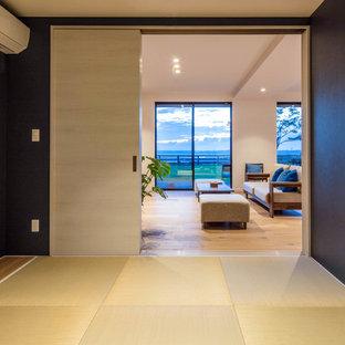 Esempio di un grande soggiorno moderno aperto con pareti bianche, pavimento in tatami e TV a parete