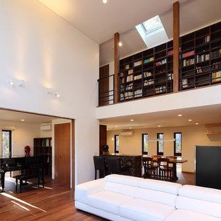 他の地域の中くらいのアジアンスタイルのおしゃれなリビング (白い壁、濃色無垢フローリング、薪ストーブ、タイルの暖炉まわり、壁掛け型テレビ、茶色い床) の写真