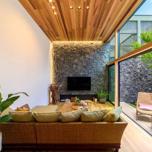 東京23区のアジアンスタイルのおしゃれなLDK (マルチカラーの壁、無垢フローリング、壁掛け型テレビ、茶色い床) の写真
