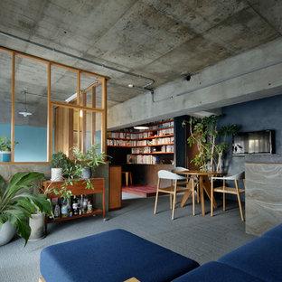 東京都下のインダストリアルスタイルのおしゃれなLDK (グレーの壁、壁掛け型テレビ、グレーの床、カーペット敷き) の写真
