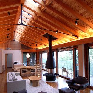 Diseño de salón abierto, moderno, grande, con paredes blancas, suelo de contrachapado, chimeneas suspendidas, marco de chimenea de piedra, televisor independiente y suelo marrón
