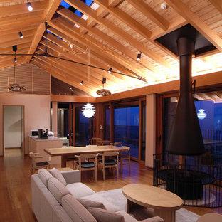 Esempio di un grande soggiorno etnico aperto con pareti bianche, camino sospeso, pavimento marrone e pavimento in legno massello medio