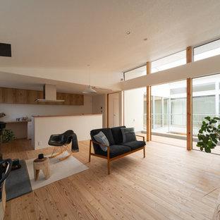 他の地域の北欧スタイルのおしゃれなLDK (白い壁、淡色無垢フローリング、薪ストーブ、コンクリートの暖炉まわり、据え置き型テレビ) の写真