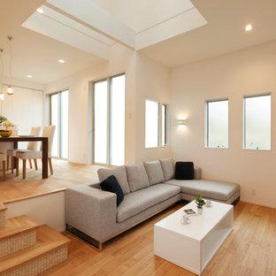 他の地域のモダンスタイルのおしゃれなリビング (白い壁、無垢フローリング、据え置き型テレビ、茶色い床) の写真